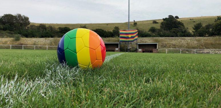 A rainbow striped football on a football pitch