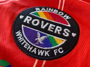 The Rainbow Rovers crest on the 2021 red Rainbow Rovers home shirt