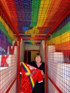 Sophie Cook in the tunnel at the Enclosed Ground, Whitehawk with the 2021 Rainbow Rovers Shirt. Rainbow flags surround the tunnel.