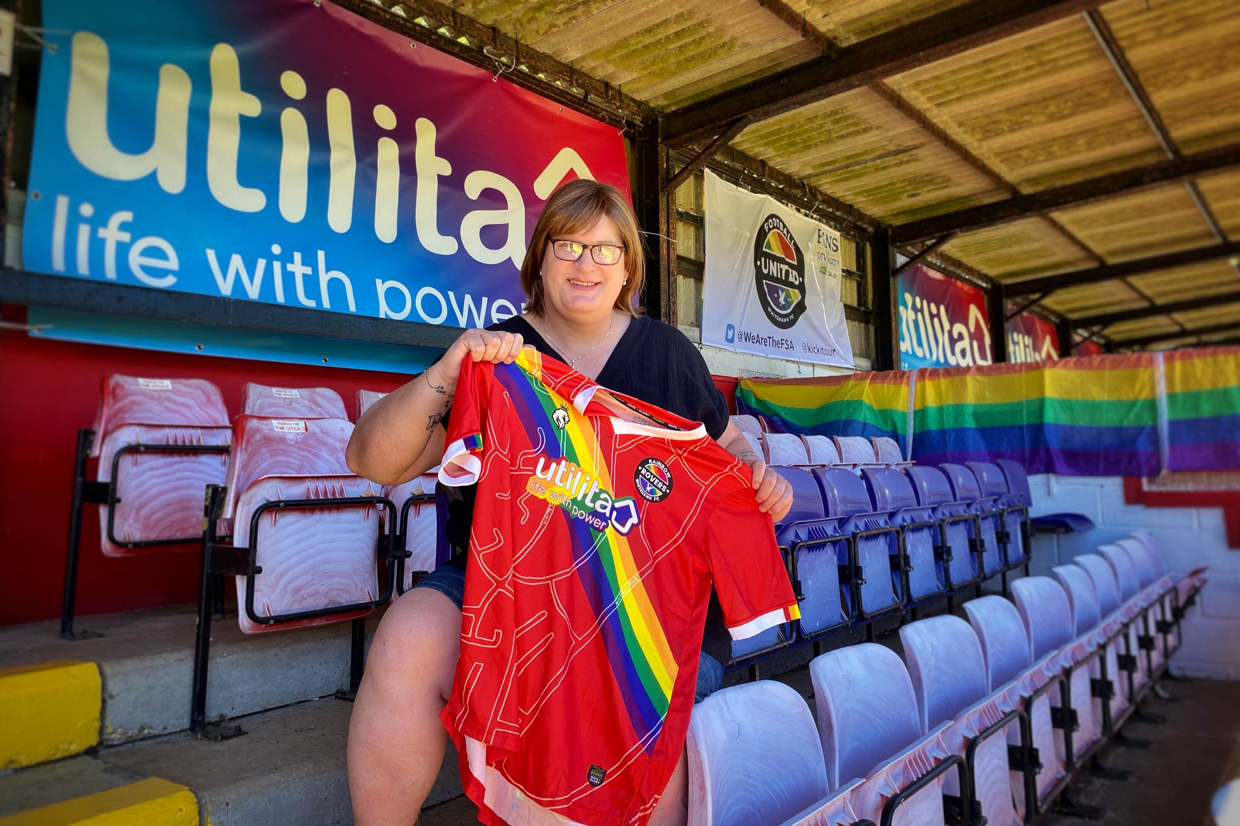 Sophie Cook in the stand at the Enclosed Ground, Whitehawk with the 2021 Rainbow Rovers Shirt