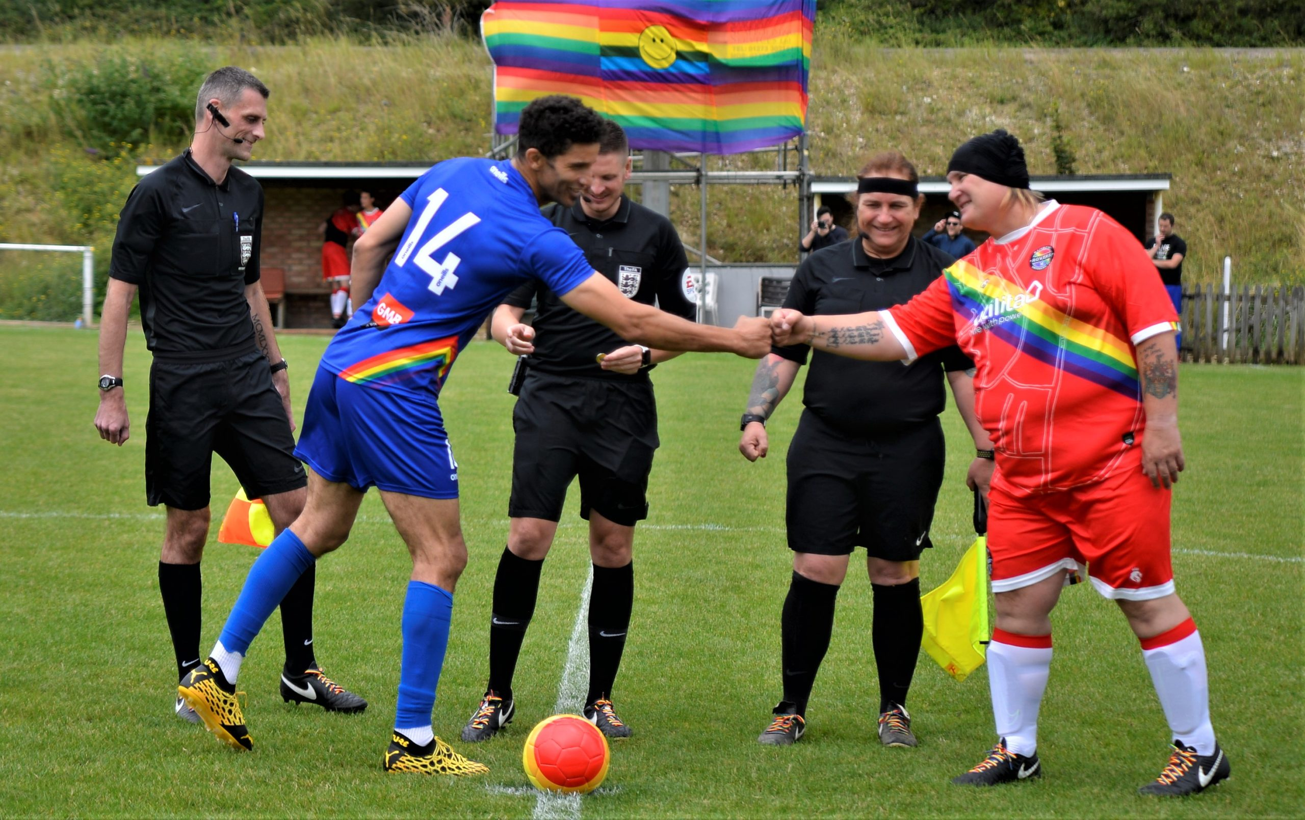 David James and Sophie Cook shake hands in front of officials and the rainbow flag ahead of the second Football United game