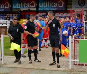 Match officials lead out the teams